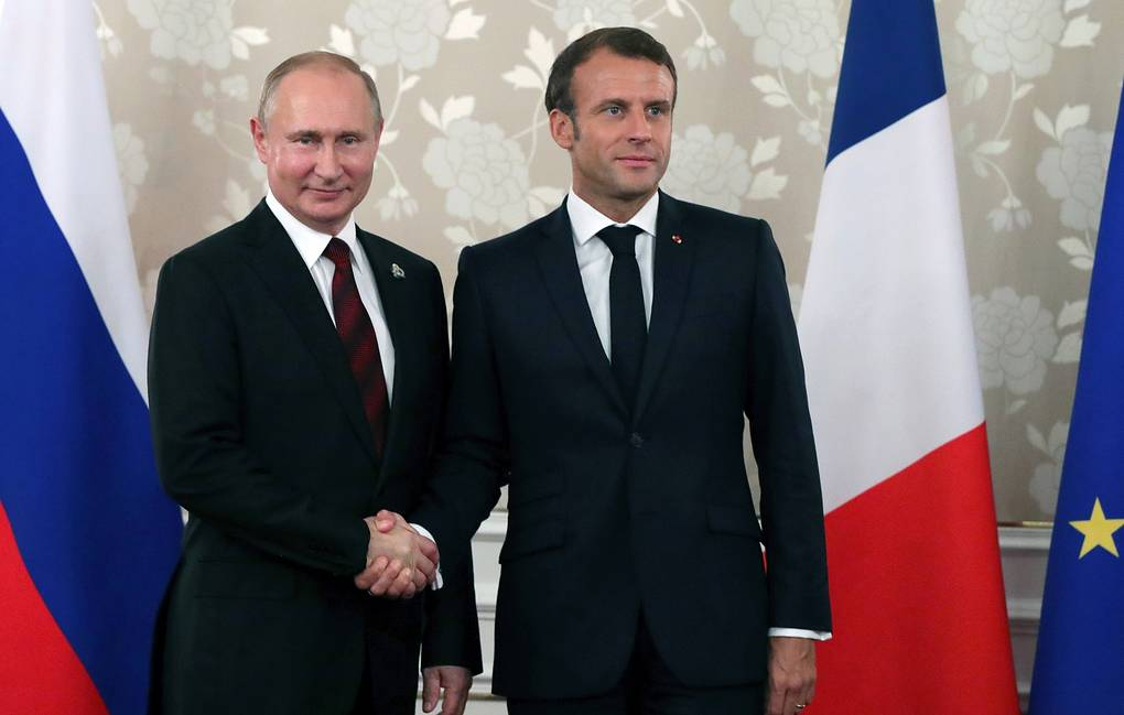 Vladimir Putin gives French first lady Brigitte Macron bouquet of roses