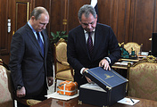 Russia's president Vladimir Putin and defense minister Sergei Shoigu looking at the black box from the Su-24 jet downed by Turkey