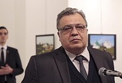 Andrei Karlov, the Russian Ambassador to Turkey pictured moments before a gunman opened fire on him. The gunman is seen at rear on the left