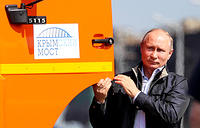 Russian President Vladimir Putin climbs into the cab of a Kamaz to spearhead a convoy of trucks over the Crimean Bridge, Kerch, May 15. The newly-built bridge linking Crimea to mainland Russia was opened to automobile traffic in both directions on May 16