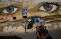 A woman walks past the a murales by British street artist My Dog Sighs, in Rome's Trastevere neighborhood, September 24