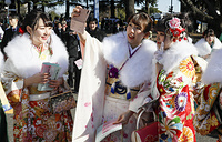 Kimono-clad 20-year-old Japanese women pose for selfies following a ceremony to celebrate Coming-of-Age Day at Toshimaen amusement park in Tokyo