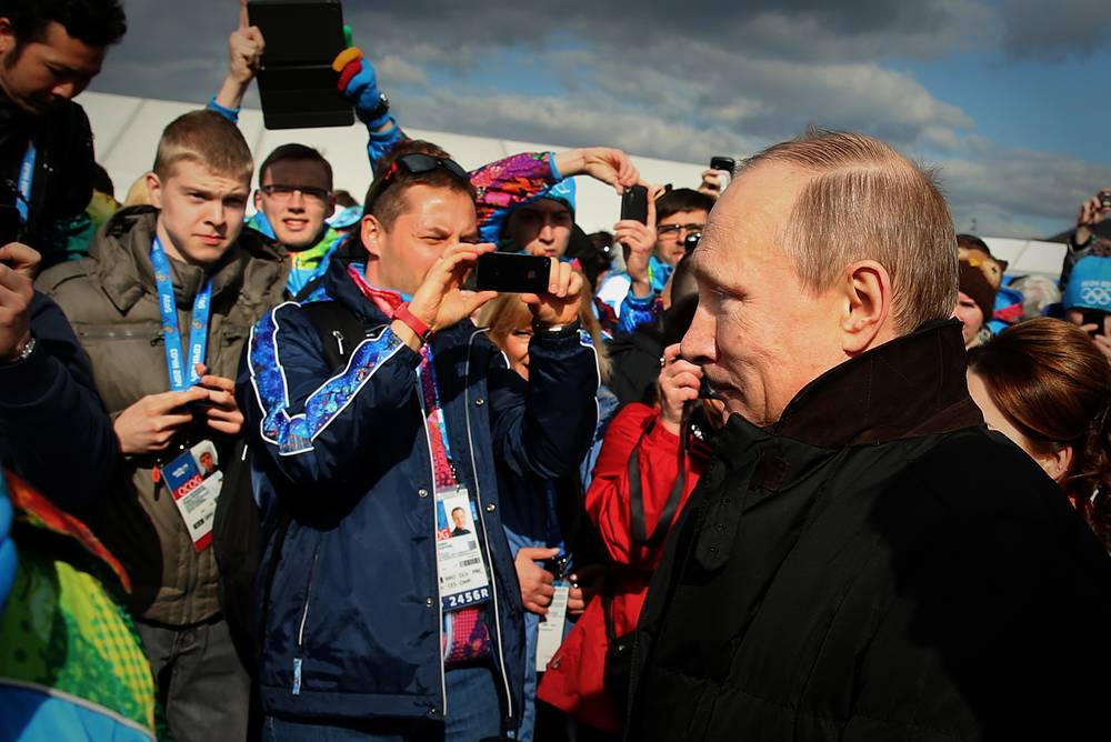 Russia's president Vladimir Putin (R) visiting the Olympic village in the coastal cluster