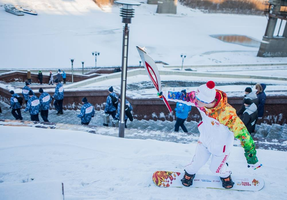 A snowboarder with an olympic torch in Russia's Tyumen