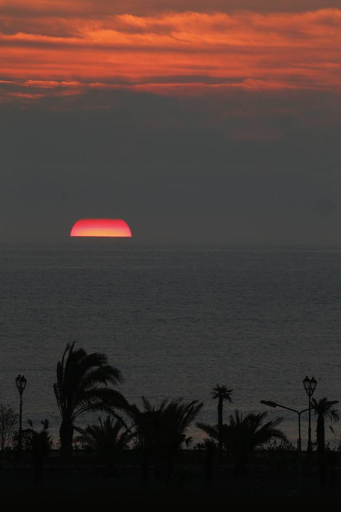 The sun peeks through low clouds while setting over the Black Sea seen from the Bolshoy Ice Dome in Sochi
