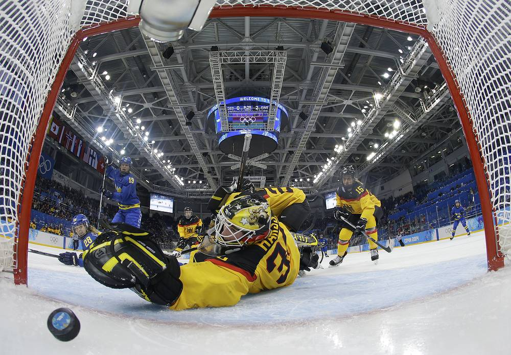 Goalkeeper Jennifer Harss of Germany reaches for the puck as Johanna Olofsson's of Sweden shot get by her for a goal during the third period of women's ice game at Shayba Arena