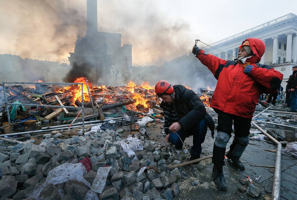 A protester uses a catapult during clashes with riot police in downtown Kiev
