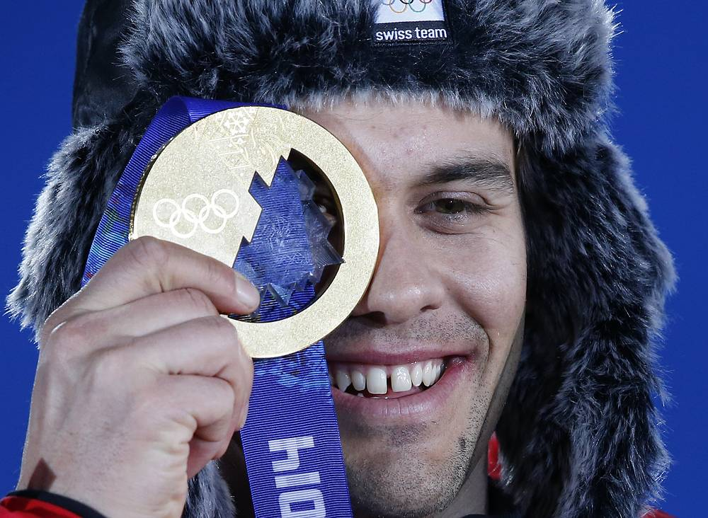The design of Olympic medals in Sochi lets you look at the world through the madal, like Gold medalist Sandro Viletta of Switzerland is doing in this photo