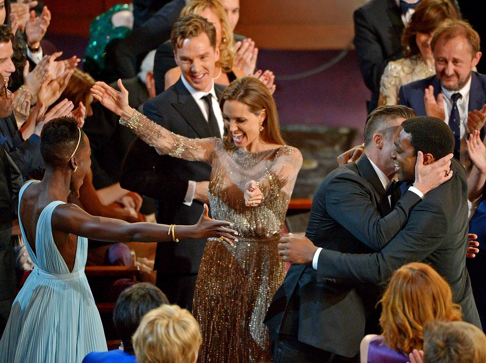 Lupita Nyong'o, left, prepares to embrace Angelina Jolie, as Benedict Cumberbatch, background center, looks on, and Brad Pitt, embraces Chiwetel Ejiofor, right