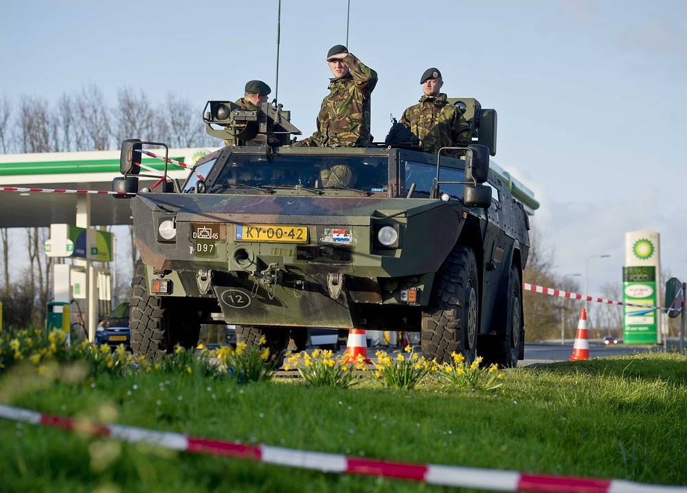 Dutch soldiers in an armored vehicle stand guard along a highway