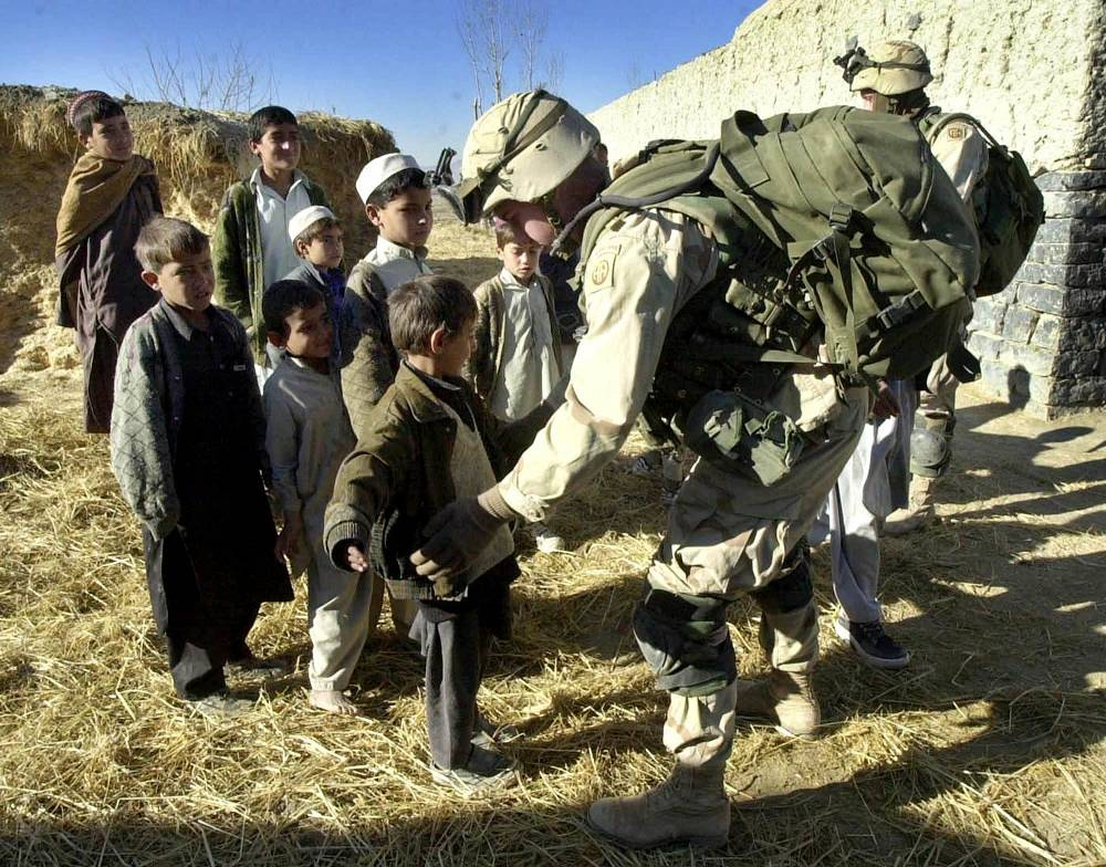 NATO heads the ISAF international security mission in Afghanistan in 2003. Photo: NATO soldier searching a child in the village of Host, Afghanistan