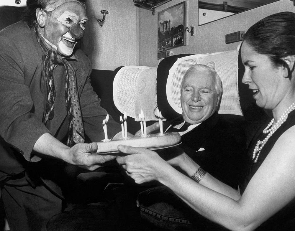 Circus artists congratulate Chaplin on his 75th birthday (Oona O'Neill beside Charlie Chaplin) in 1964
