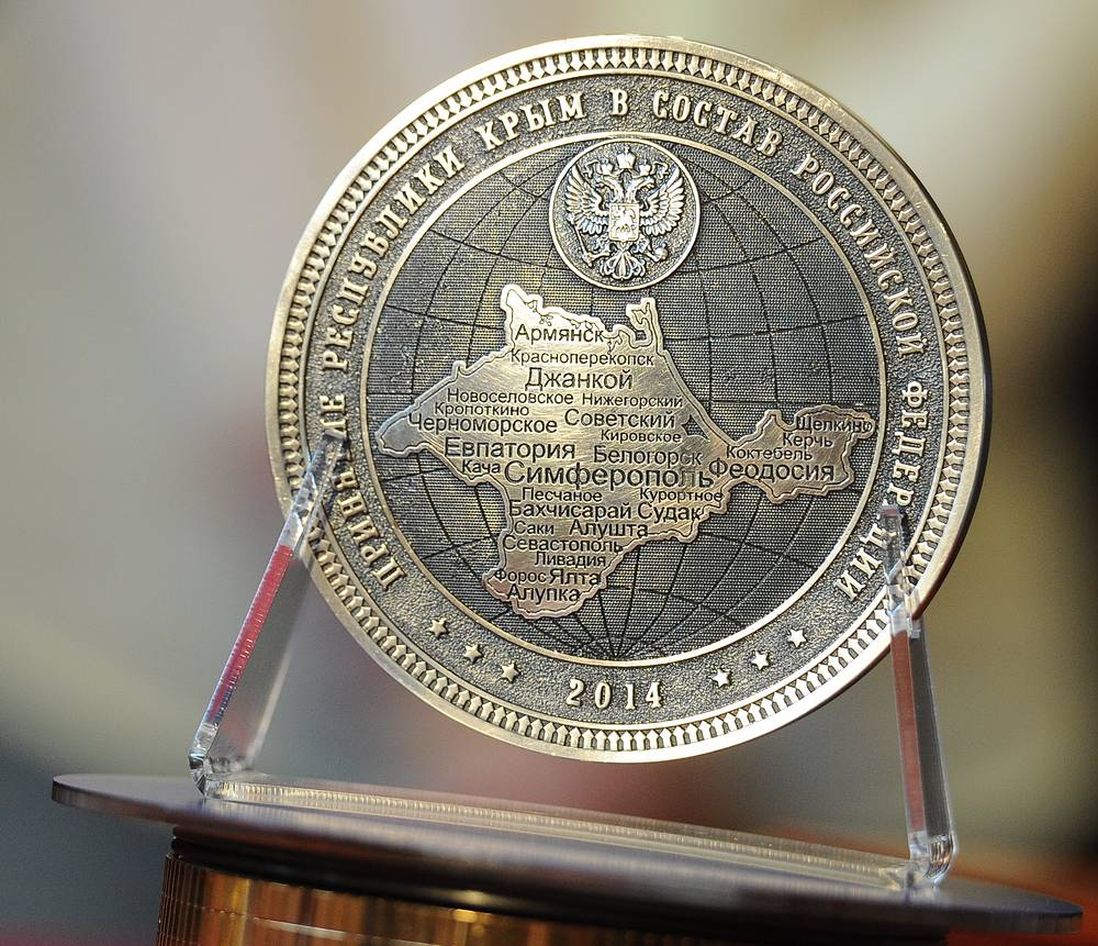 On the reverse side, there's a symbolic globe with a contour of Crimea, including 28 settlements and cities