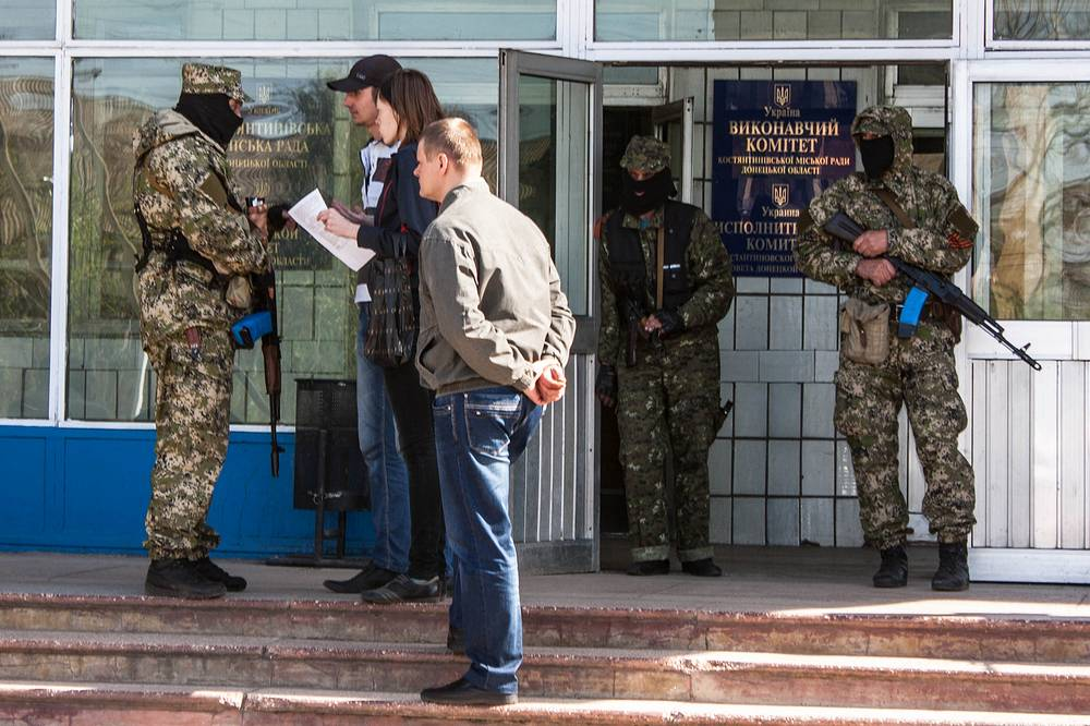 Masked armed men guard at the city hall in Kostiantynivka