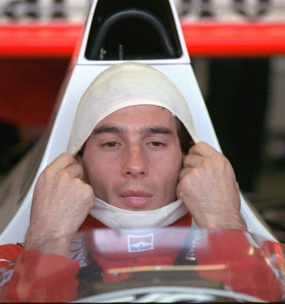 In 1994 Senna started competeing for Williams. Photo: Ayrton Senna, in a McLaren Honda, pulls on a fire resistant mask before going out to practice for the Australian Grand Prix