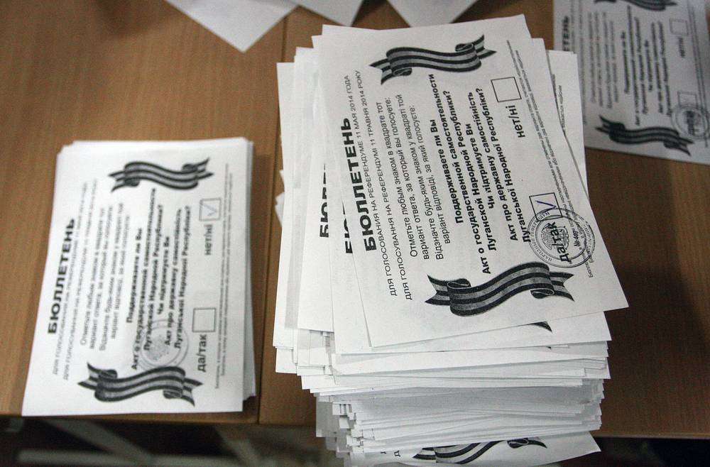 Two piles, with 'Yes' votes (R) and 'No' votes (L), seen during a vote count in Luhansk