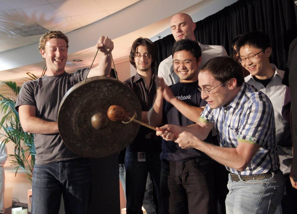 Field software engineer Ben Gerzfield hits a gong as Mark Zuckerberg holds it to launch the social network site's new localization services  during a press conference in Palo Alto