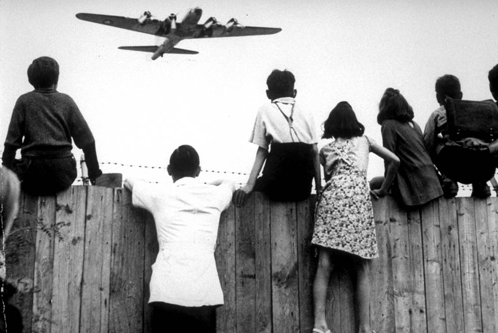 As the Cold War started, the occupation zones began to merge, leaving the Soviet and the Western Allied zone, surrounded by East German territory. Photo: West Berlin children watch US airplanes during the Berlin Airlift, that stopped the Soviet blockade