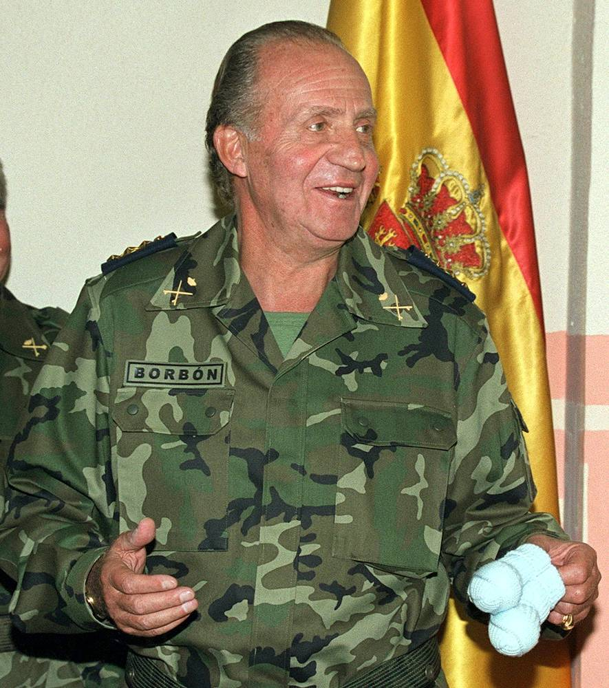 Spanish King Juan Carlos holds bootees given to him as a gift for his second grandson in 1999