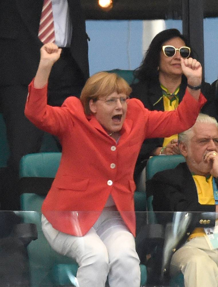 German Chancellor Angela Merkel celebrates Germany's 2-0 goal during the FIFA World Cup 2014 group G preliminary round match between Germany and Portugal