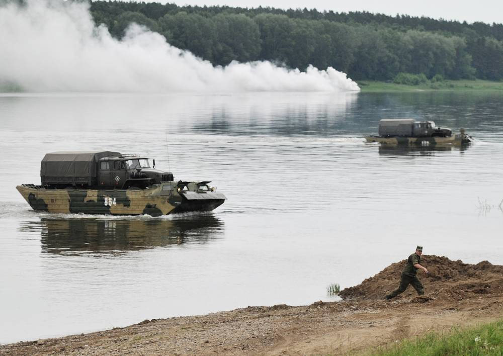 Military vehicles transported over a river