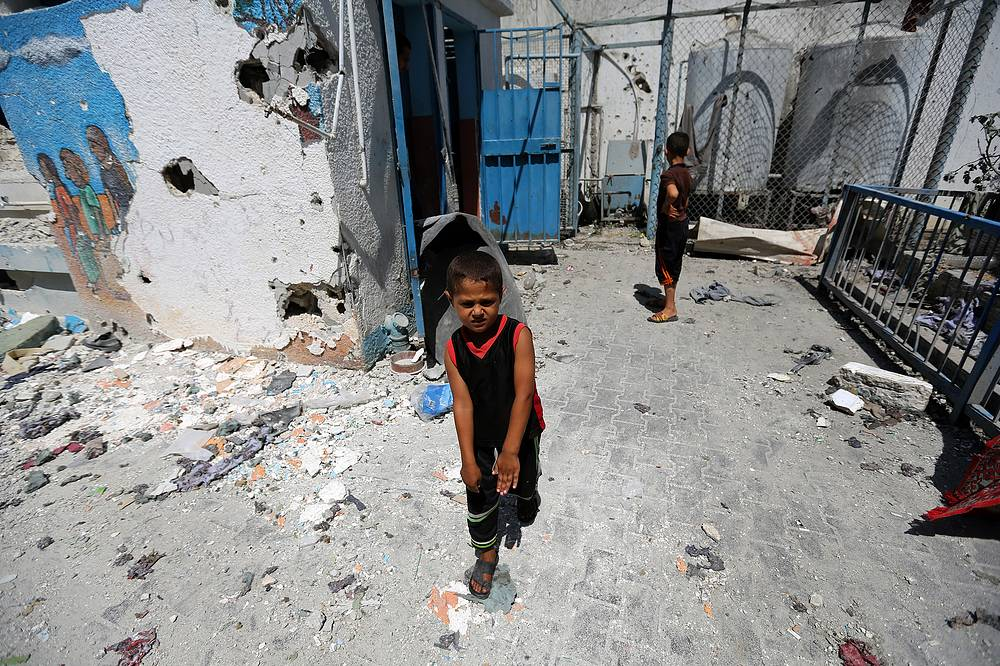Palestinian children play next to a destroyed classroom at a UN school in Jabalia