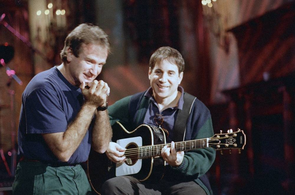 Actor Robin Williams plays a harmonica as singer Paul Simon plays a guitar on the set of the 'Saturday Night Live' show