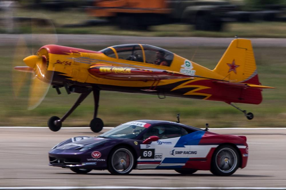 A Yak-54 training aircraft of the First Flight aerobatics team and a Ferrari 458 Italia compete during the Forsazh (Boost) car and air show