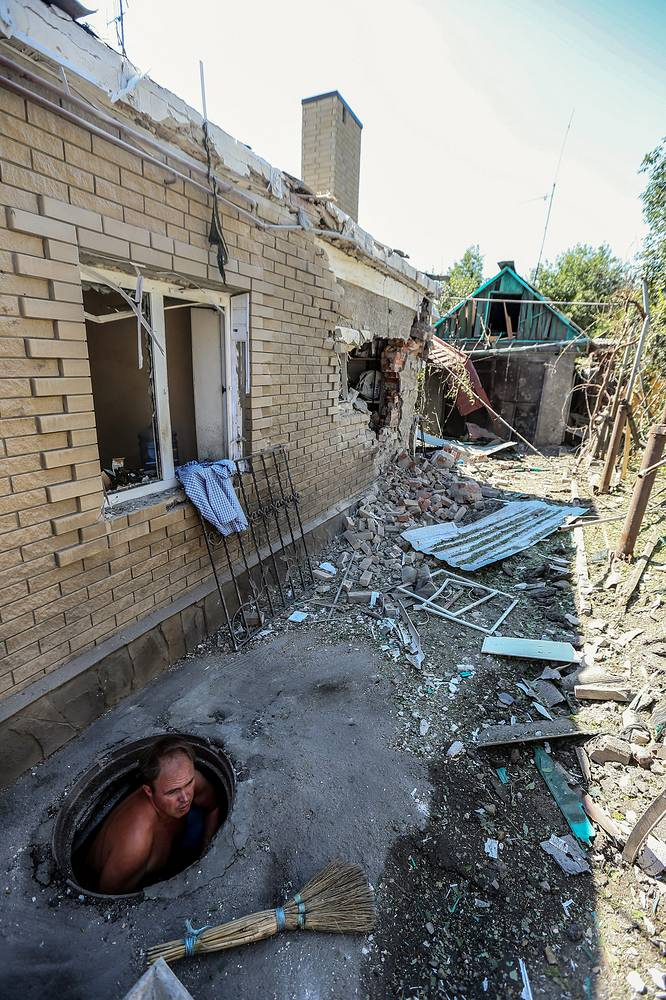 Shelling attacks of the Ukrainian military continue destroying Donetsk. Photo: a man gets out of his shelter after after a shelling attack on Donetsk