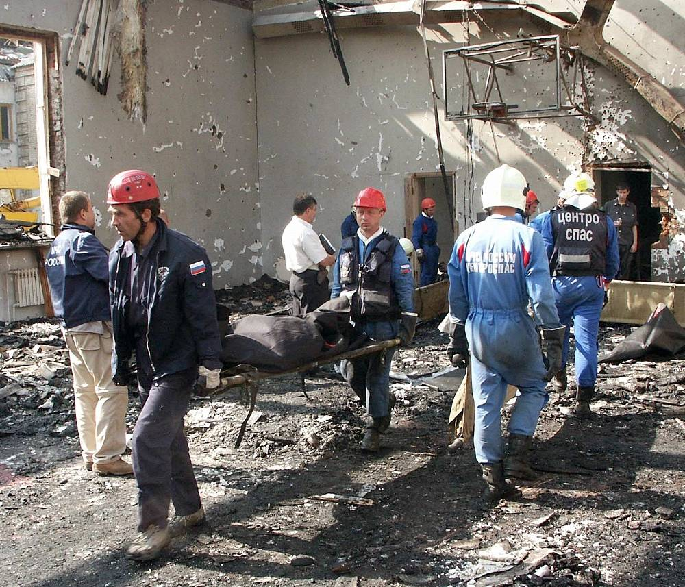 Rescue workers carry out bodies of victims of the terrorist attack on September 4, 2004