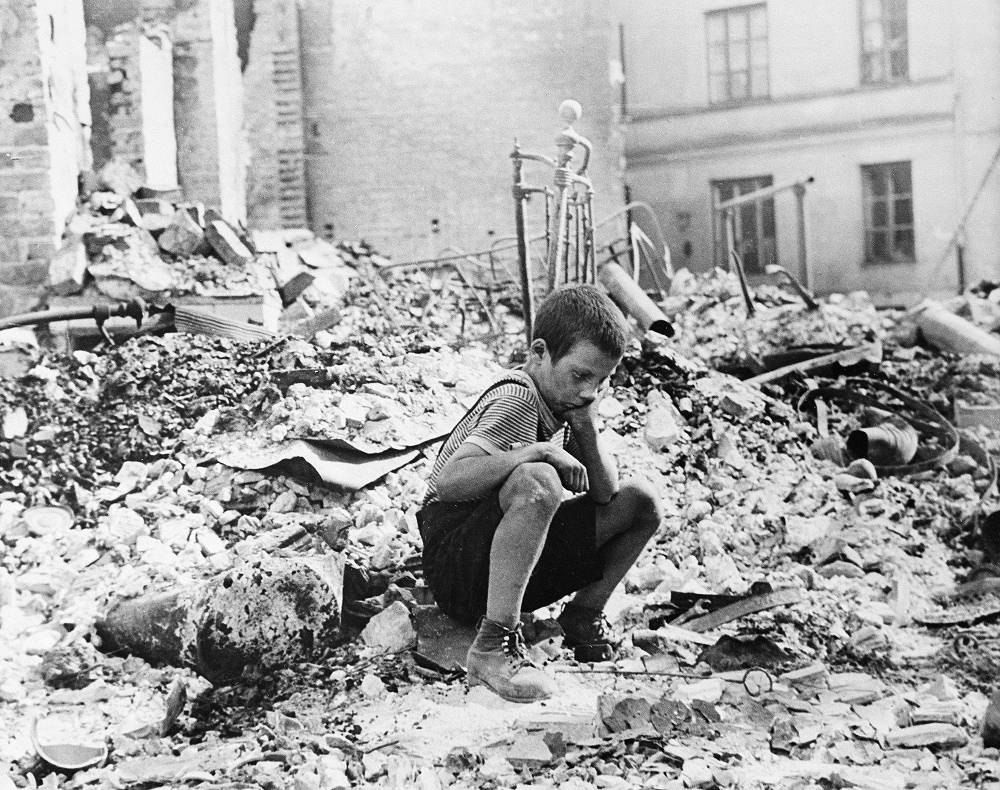 A boy sits on the ruins of his house after a German air-raid on Warsaw in September 1939