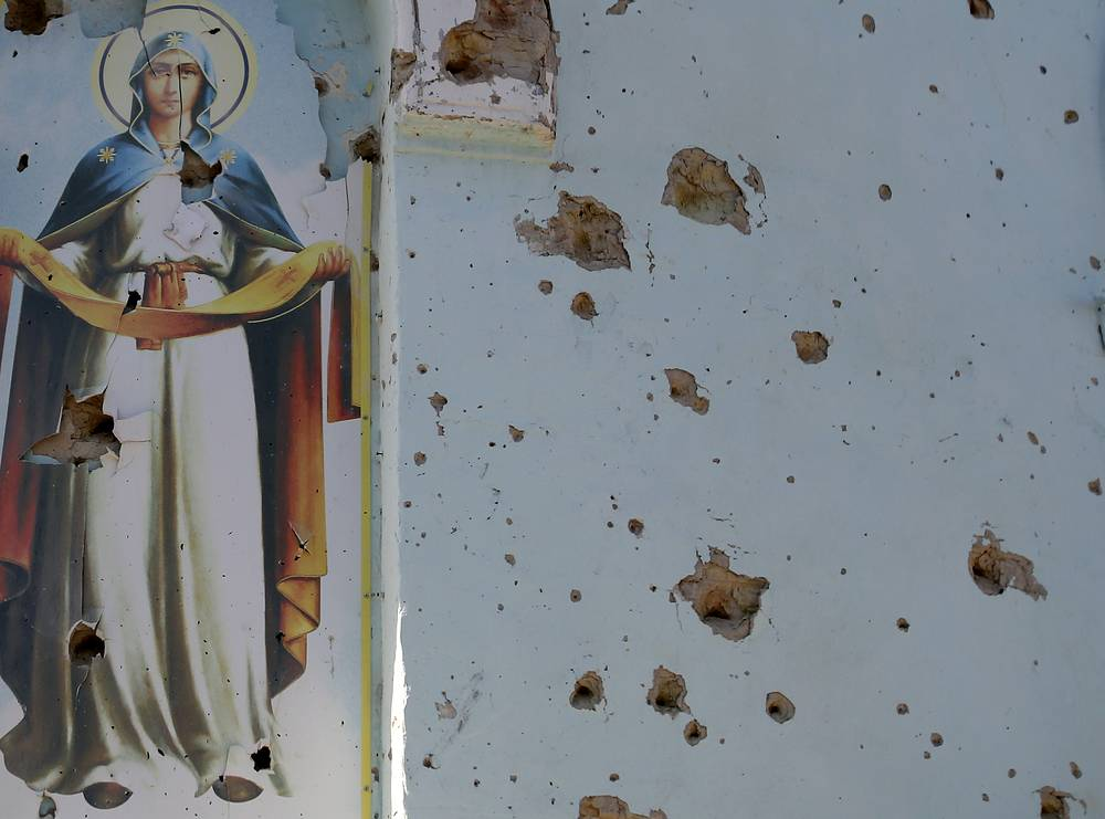 The most recent UN report says no less than 3,171 have been killed and over 8,000 have been wounded in the armed conflict in eastern Ukraine since its beginning in April. Photo: an icon damaged by bullets is seen in a village church in eastern Ukraine