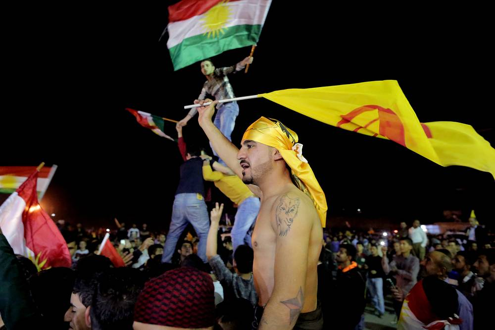 According to regional observers, the allowance of Peshmerga convoy to enter Kobani will increase the role of the Syrian and Iraqi Kurds in opposition to the Islamic state in the international coalition against terrorism. Photo: supporters of Kurdish Peshmerga forces celebrate as they wait for the troops to cross the border into Turkey en route to Kobani