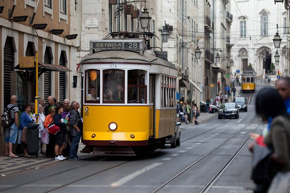 Photo: people queue to board a tram in downtown Lisbon, 2011