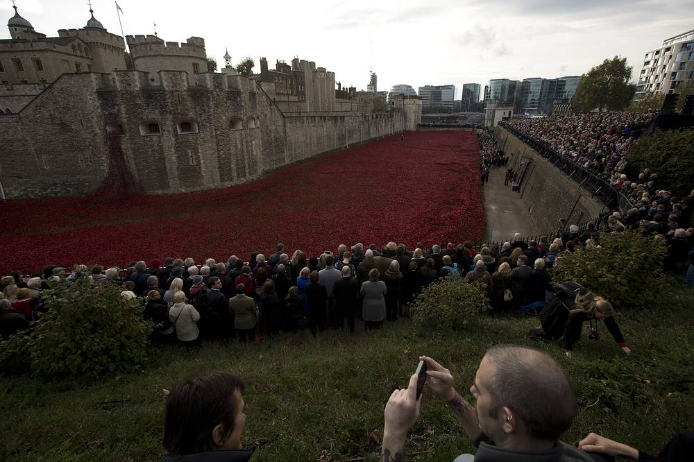Photo: People stand together before observing a two minutes silence during a remembrance day ceremony, London, November 11, 2014