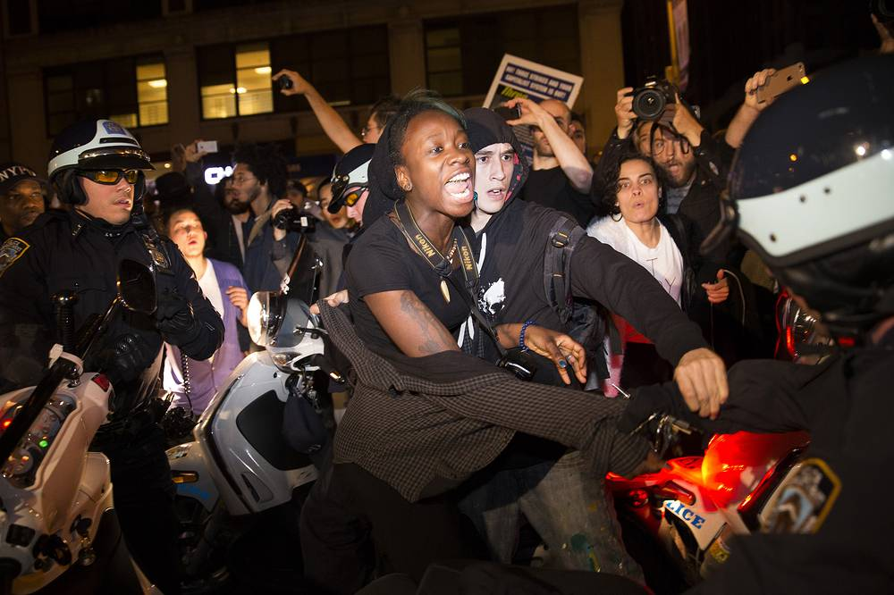 Photo: A protestor scuffles with police during a march towards Times Square after the announcement of Ferguson's grand jury decision, in New York.
