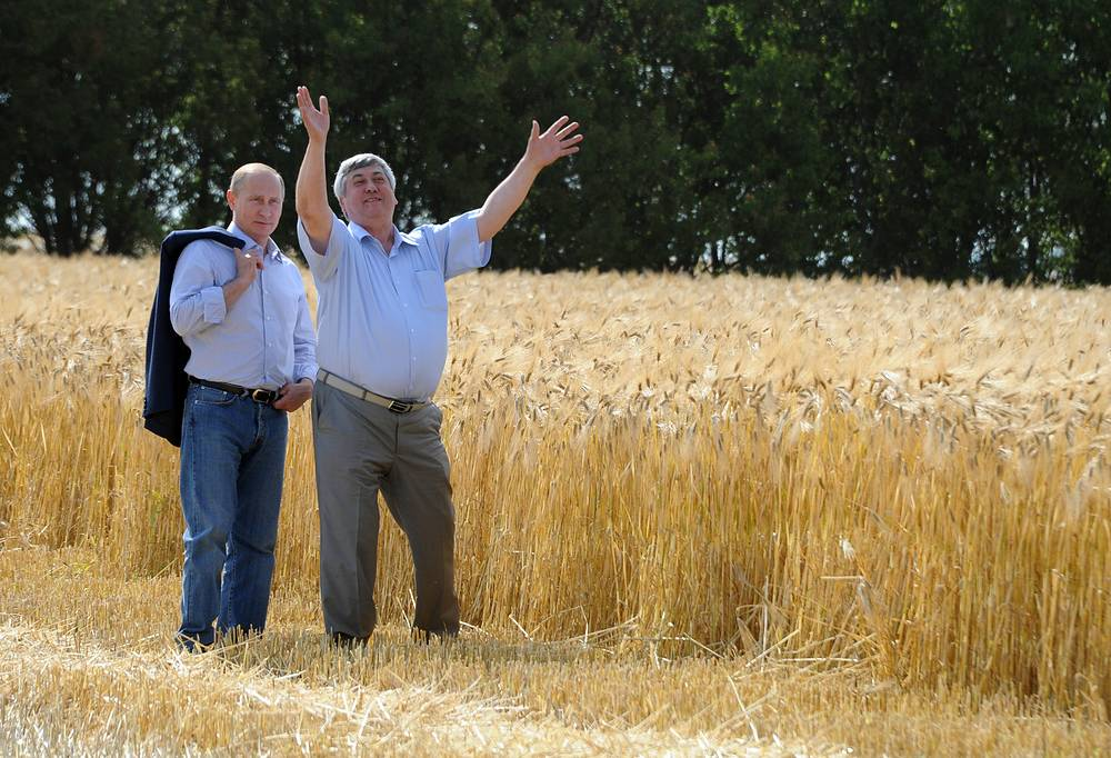 Sergey Pyanov, the head of the Rossiya Agricultural Cooperative, and Russian President Vladimir Putin (right) take a walk in a field