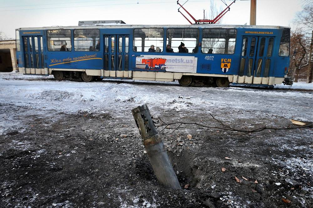 Photo: A tram goes past a Grad missile remnant in the city of Donetsk