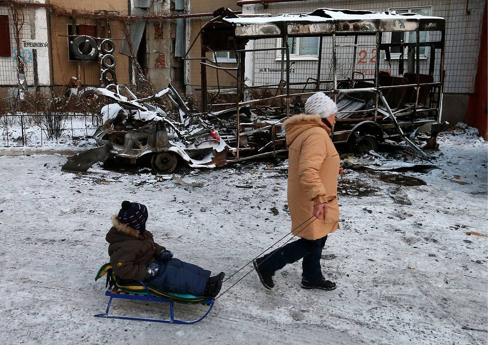 Silence regime in eastern Ukraine began at 09:00 a.m. local time December 9. Photo: Donetsk residents pass by a burnt out bus after a shelling attack