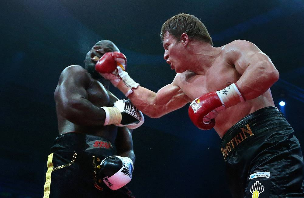 Russian boxer Alexander Povetkin (right) punches Carlos Takam of Cameroon during their heavyweight bout in Moscow