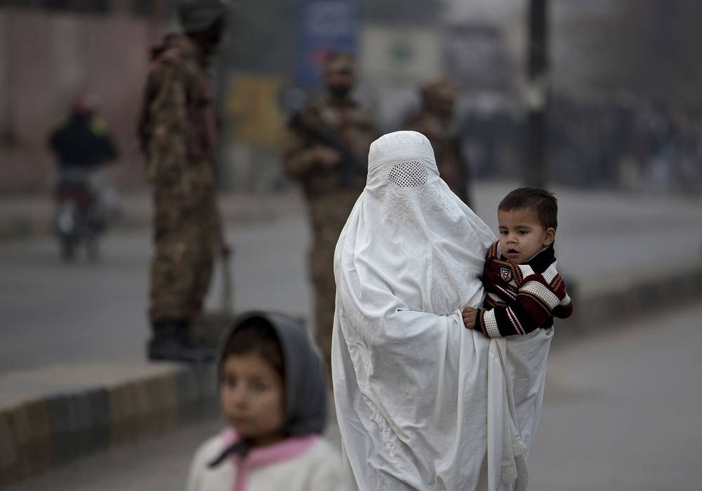 Photo: A Pakistani woman walks past a school attacked by the Taliban in Peshawar