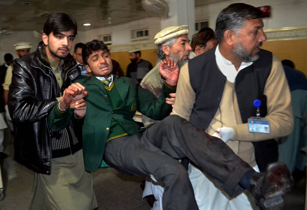 Photo: Pakistani volunteers carry a student injured in the shootout at a school under attack by Taliban gunmen in Peshawar