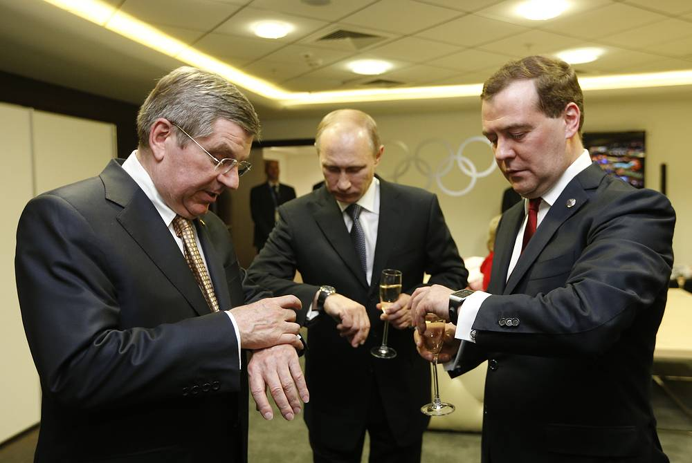 IOC President Thomas Bach, Russian President Vladimir Putin and Prime Minister Dmitry Medvedev look at their watches before the closing ceremony of the 2014 Winter Olympics in Sochi