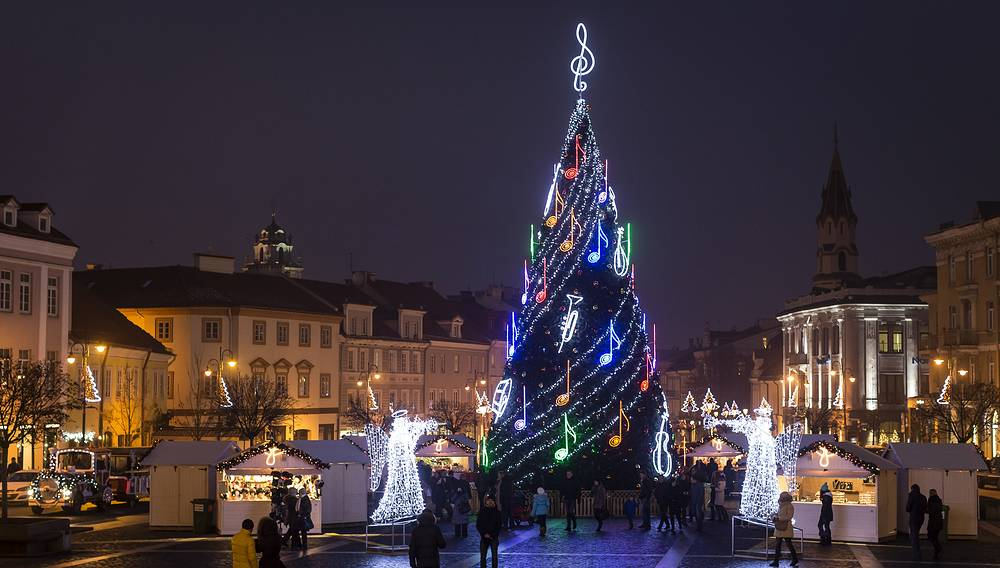 People stroll around a Christmas tree in the Old city in Vilnius, Lithuania