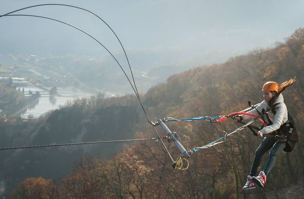 Girl rides Sochi Swing, the world's highest rope swing over the gorge of the Mzymta River at Skypark in Sochi