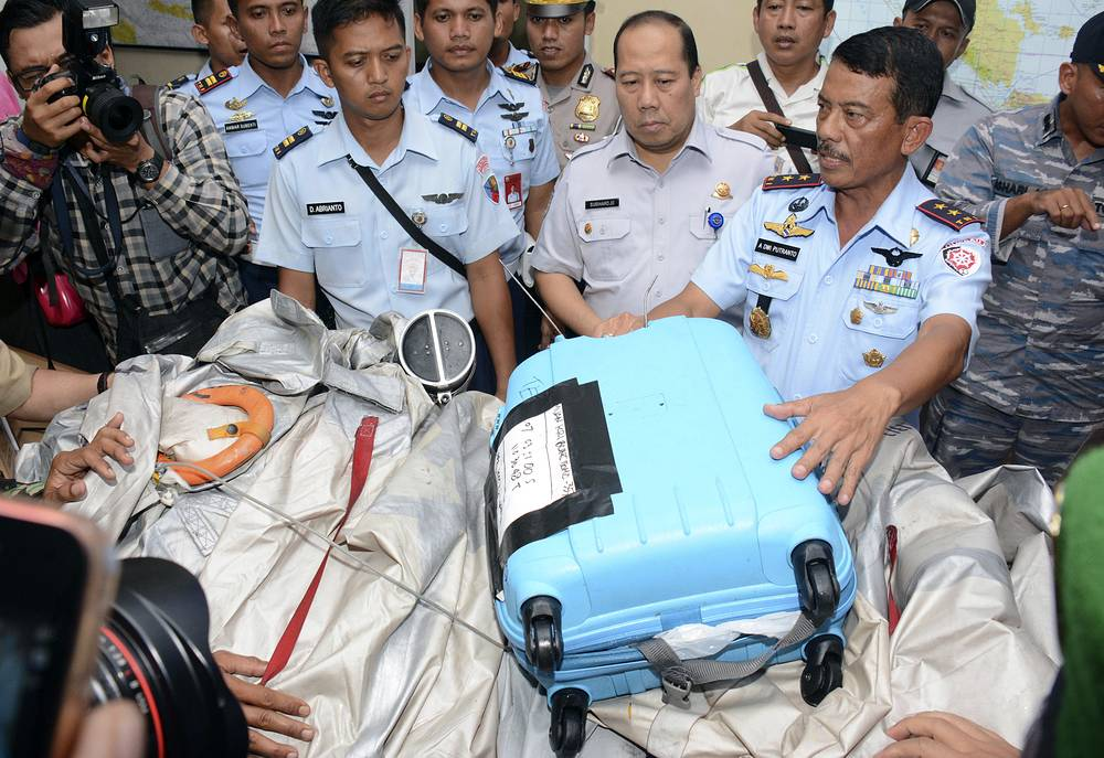 Photo: Airplane parts and a suitcase found floating on the water near the site where AirAsia Flight 8501 disappeared