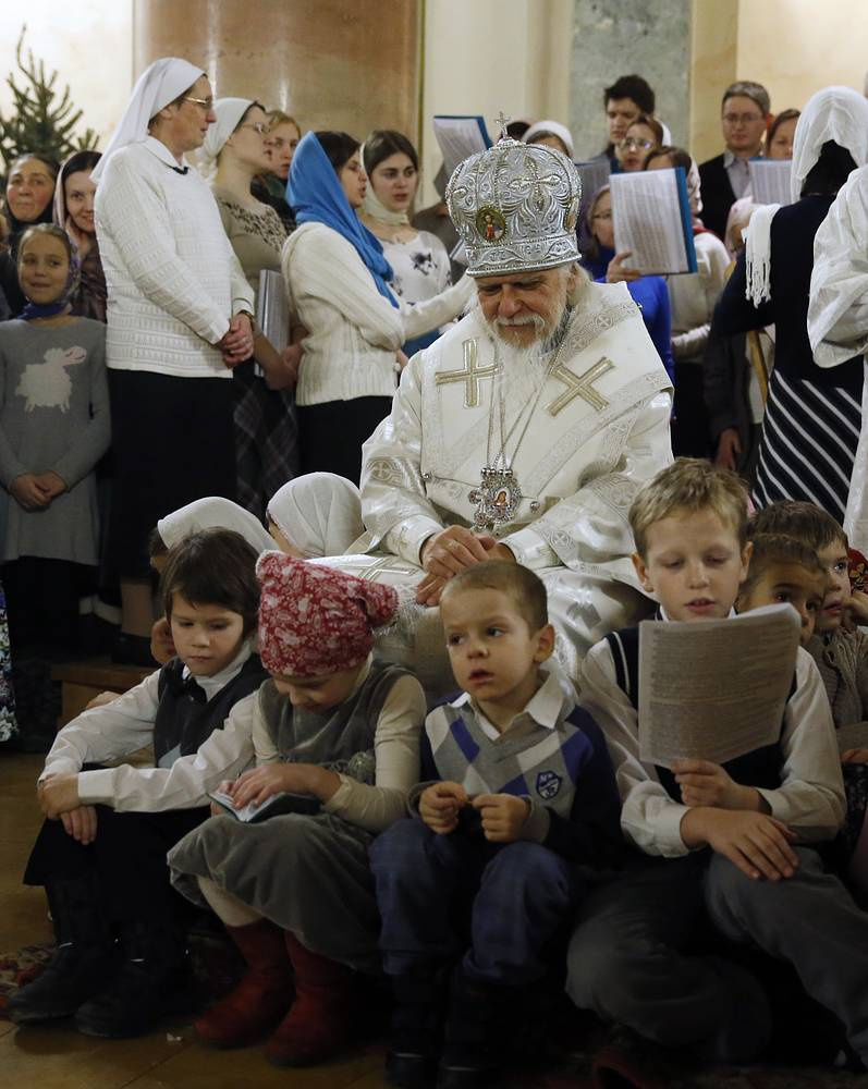 Russian Orthodox Church bishop Panteleimon prays next to children during a Christmas church service in Moscow, Russia