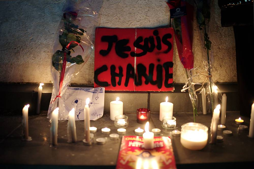"A banner reading ""I am Charlie"" is displayed with candles during a gathering to pay respect for the victims of a terror attack against a satirical newspaper, in Paris, France"