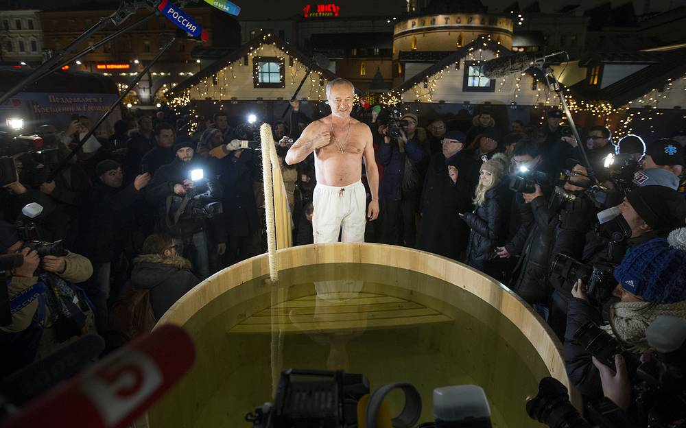 A man gets ready to take a dip into a basin with ice water during celebrations of the Orthodox Epiphany in Moscow's Revolution Square