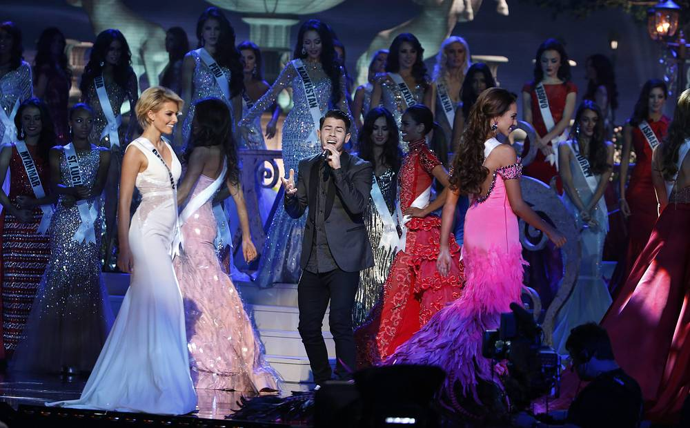 US singer Nick Jonas performing onstage amongst contestants during the evening gown competition at the 2014 Miss Universe Final